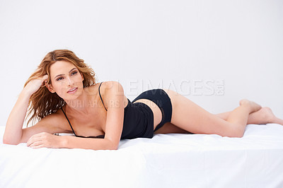 Buy stock photo Portrait of a woman in lingerie lying down and posing seductively