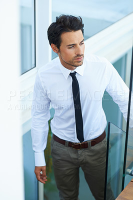 Buy stock photo A handsome young businessman walking up the stairs