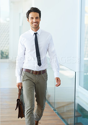 Buy stock photo A handsome young businessman walking with his suitcase