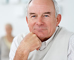 Closeup portrait of a retired man with hand on chin