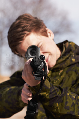 Buy stock photo A young soldier aiming his rifle at you