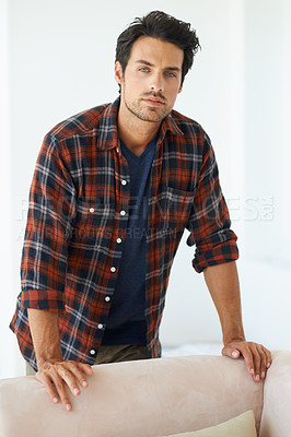 Buy stock photo Portrait of a gorgeous young man standing behind a sofa and looking at the camera