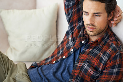 Buy stock photo A gorgeous young man lying on a sofa at home with hand rested behind his head