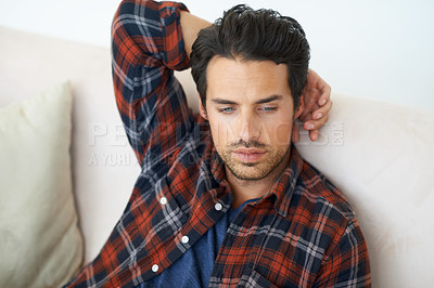 Buy stock photo A gorgeous young man sitting on a sofa at home with hand rested behind his head