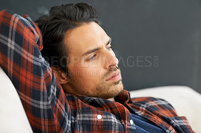 Buy stock photo A gorgeous young man lying on a sofa with arm behind his head and gazing into the distance with an expression of contemplation on his face