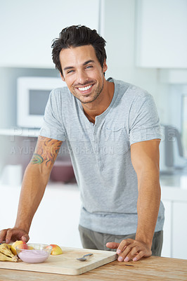 Buy stock photo Portrait of a gorgeous young man leaning against a kitchen counter and smiling