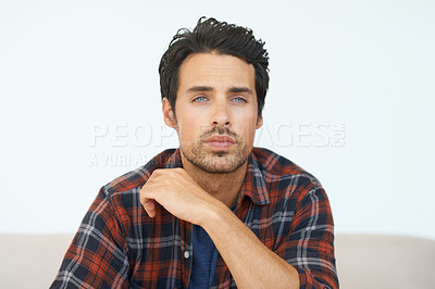 Buy stock photo A gorgeous young man sitting on a sofa staring into the distance