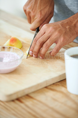 Buy stock photo Cropped shot of a man slicing an apple on a cutting board with a bowl of yogurt in front of him
