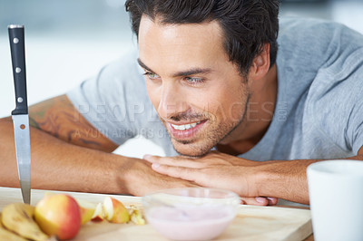 Buy stock photo A gorgeous young man with arms rested on a kitchen counter and chin rested on hand, playfully looking at a knife stuck point down into a cutting board