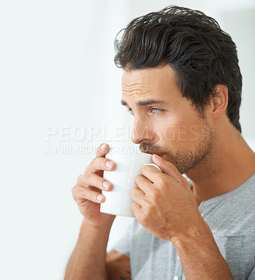 Buy stock photo Profile of a gorgeous young man sipping on a cup of coffee at home