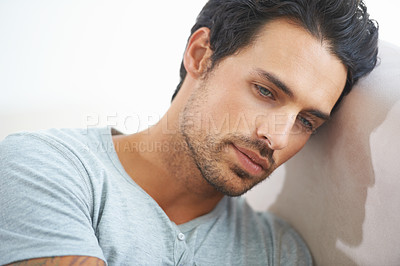 Buy stock photo A gorgeous young man resting on a sofa at home with a somber expression