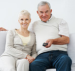 Retired couple watching television at home