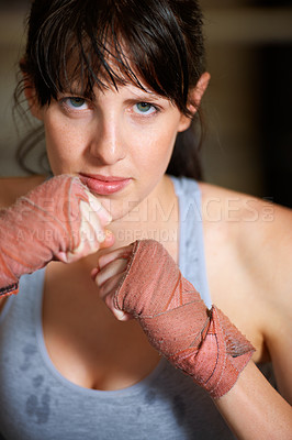 Buy stock photo Portrait of a determined female boxer standing ready to fight