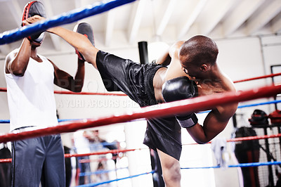 Buy stock photo A kickboxer launching a high kick at his sparring partner's gloves