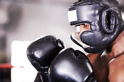 Buy stock photo A young boxer in protective gear watching for his opponent's next move