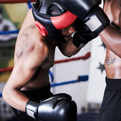 Buy stock photo A boxer ducking to deliver a punch to his opponents midriff