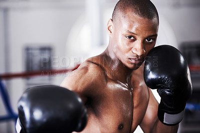 Buy stock photo An african american boxer with his gloves up standing in the ring