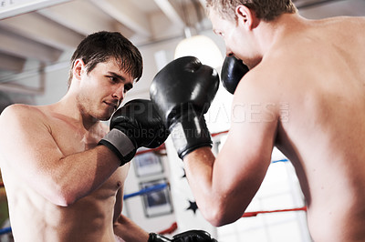 Buy stock photo Two young boxers fighting it out in the ring