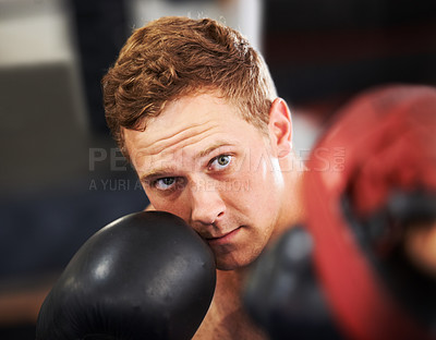 Buy stock photo A young boxer throwing a punch at his partner's sparring glove