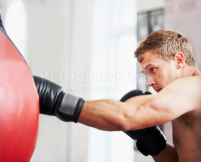Buy stock photo A young boxer practicing with a punching ball