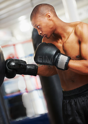 Buy stock photo An african american boxer practicing with a punching bag at the gym