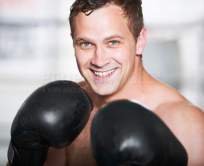 Buy stock photo A young handsome boxer smiling at you with his gloves up