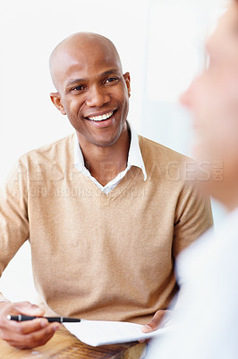 Buy stock photo A handsome african american man smiling at a colleague while working on a budget
