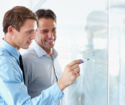 Buy stock photo Two businesspeople working on a whiteboard together