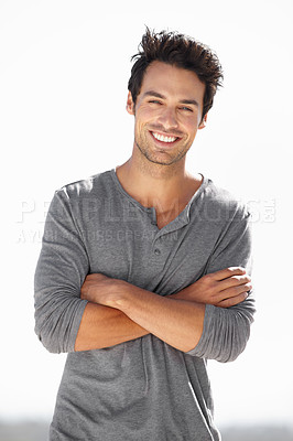 Buy stock photo Portrait of a handsome young man standing confidently with his arms folded