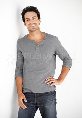 Buy stock photo Portrait of a handsome young man leaning against a wall with his hand on his hip