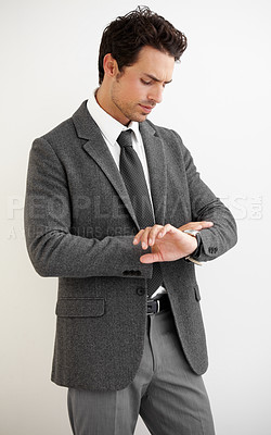 Buy stock photo A handsome young businessman looking at his watch