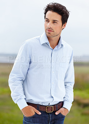 Buy stock photo A handsome young model standing outside with his hands in his pockets