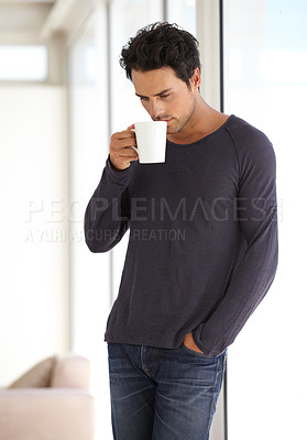 Buy stock photo A handsome young man sipping his morning coffee