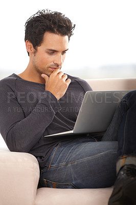 Buy stock photo A handsome young man thinking while working on his laptop