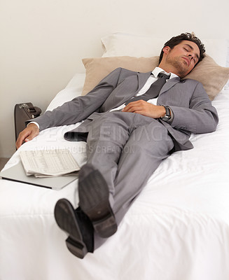 Buy stock photo A handsome young businessman asleep on the bed with his digital tablet