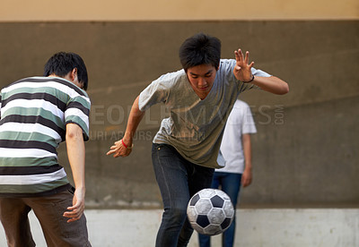 Buy stock photo Young asian males playing soccer outside
