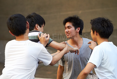 Buy stock photo Asian teen shoving his friend while another tries to break up the fight