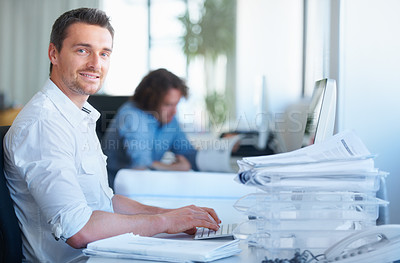Buy stock photo Cropped shot of a businessman working in the office with his colleague in the background