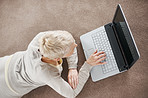Top view of a woman using a laptop while lying on the floor