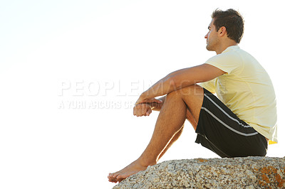 Buy stock photo Profile of a young man sitting on a rock - copyspace