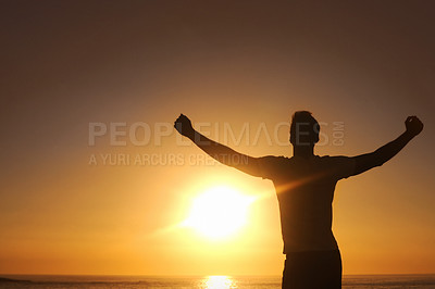 Buy stock photo Silhouette of a man with his arms outstretched with the sunset in front of him