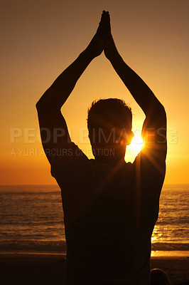Buy stock photo Silhouette of a man against the sunset with his arms raised in a yoga pose