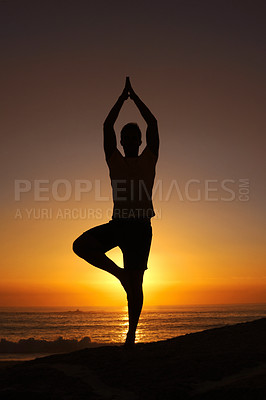 Buy stock photo Silhouette of a man balancing on his one leg with a sunset in the background