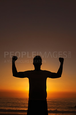 Buy stock photo Silhouette of a man standing with his arms victoriously raised against the sunset