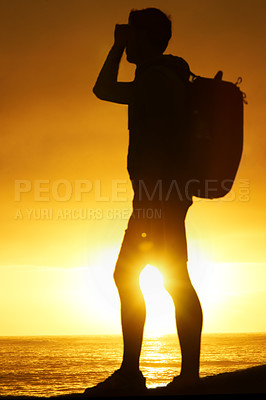 Buy stock photo Silhouette of a hiker standing and looking over the ocean