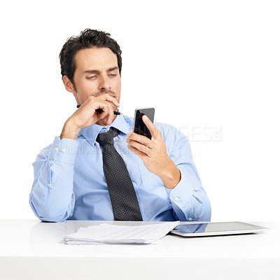 Buy stock photo Young businessman sitting at his desk and checking his cellphone