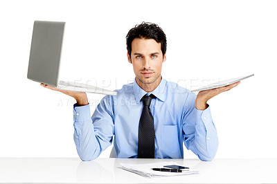 Buy stock photo A young businessman comparing a laptop to a digital tablet