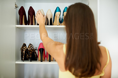 Buy stock photo Rearview of a woman reaching for a pair of shoes in her wardrobe