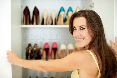 Buy stock photo Portrait of an attractive young woman looking standing infront of her shoe closet