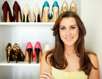Buy stock photo Portrait of a confident young woman standing infront of a wardrobe full of shoes